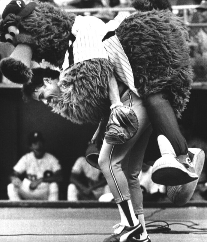 FILE - In this July 12, 1983, file photo, the Phillie Phanatic jumps onto the back of Atlanta Braves catcher Biff Pocoroba, who didn't see the Phillies mascot coming a warmup before a baseball doubleheader in Philadelphia. Pocoroba, who played in the 1978 All-Star Game and was a backup on the Braves team that won an improbable NL West title in 1982, has died at age 66. (AP Photo/Rusty Kennedy, File)
