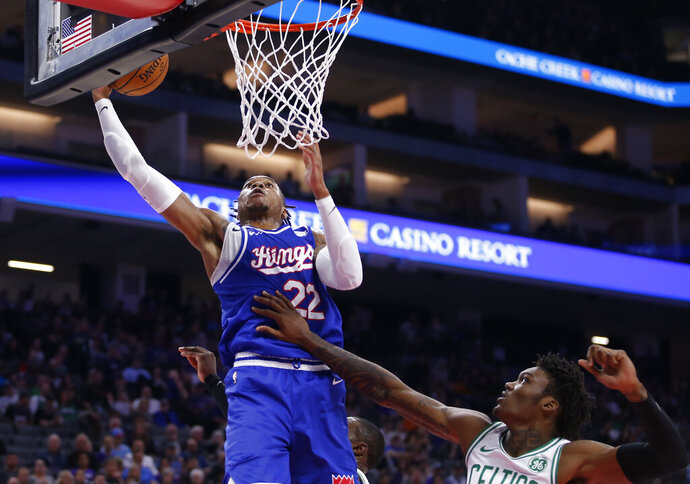 Sacramento Kings forward Richaun Holmes, left, goes to the basket against Boston Celtics center Robert Williams III during the first half of an NBA basketball game in Sunday, Nov. 17, 2019. (AP Photo/Rich Pedroncelli)