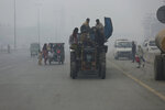 People cross a road engulfs in a smog in Lahore, Pakistan, Friday, Nov. 22, 2019. Tens of thousands of people in Pakistan's eastern city are at risk of respiratory disease because of poor air quality related to thick smog hanging over the region, an international rights group said Friday. (AP Photo/K.M. Chaudary)