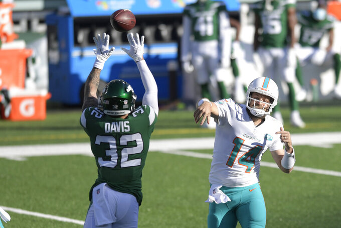 New York Jets' Ashtyn Davis (32), left, tries to block a throw from Miami Dolphins quarterback Ryan Fitzpatrick during the first half of an NFL football game, Sunday, Nov. 29, 2020, in East Rutherford, N.J. (AP Photo/Bill Kostroun)