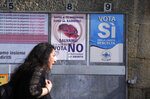 A woman walks past posters for the abortion referendum in San Marino, Sunday, Sept. 26, 2021. Tiny San Marino is one of the last countries in Europe which forbids abortion in any circumstance — a ban that dates from 1865. Its citizens are voting Sunday in a referendum calling for abortion to be made legal in the first 12 weeks of pregnancy. (AP Photo/Antonio Calanni)