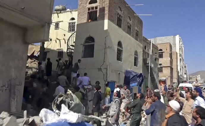In this frame grab from from video, people search in the rubble following Saudi-led coalition airstrikes that killed at least six, including children, officials said, in the residential center of the capital, Sanaa, Yemen. The Sanaa airstrikes came after Yemen's Iran-backed Houthi rebels, who control the capital, launched a drone attack earlier in the week on a critical oil pipeline in Saudi Arabia, Tehran's biggest rival in the region. (AP Photo)