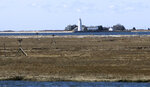 In this April 2, 2019 photo, multimillion-dollar homes and a lighthouse sit on a peninsula in Old Saybrook, Conn. The homes are among more than 900 structures on the East Coast that would become newly eligible for federal disaster aid, under a proposed remapping of coastal protection zones by the U.S. Fish & Wildlife Service (AP Photo/Dave Collins)