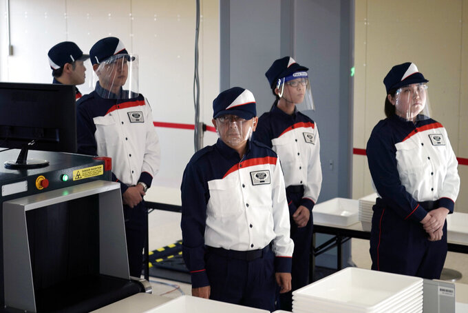 Staff members wearing face shields participate in a screening test for spectators and officials to ensure a safe and secure Toyo Olympic Games Wednesday, Oct. 21, 2020, in Tokyo. Tokyo Olympic officials say they don't know exactly what measures will be taken against the COVID-19 pandemic at next year's Games, but they want the world to know they're working on it. (AP Photo/Eugene Hoshiko)