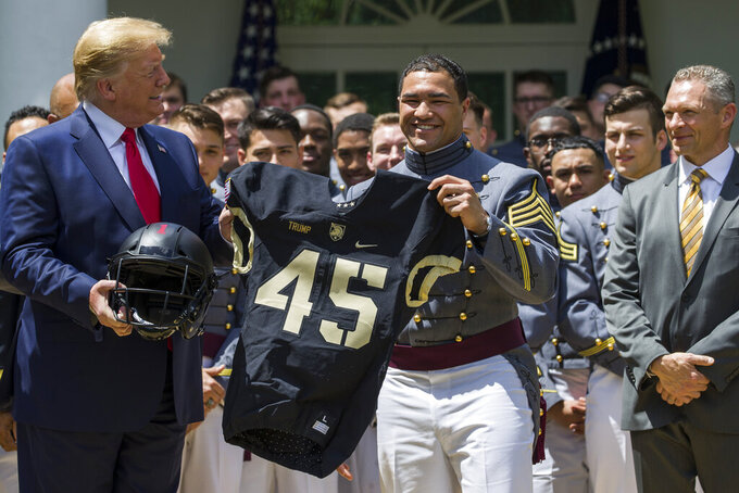 President Donald Trump accepts a jersey from Army running back Darnell Woolfolke Army during the presentation of the Commander-in-Chief's Trophy to the U.S. Military Academy at West Point football team in the Rose Garden of the White House, Monday, May 6, 2019, in Washington. (AP Photo/Alex Brandon)