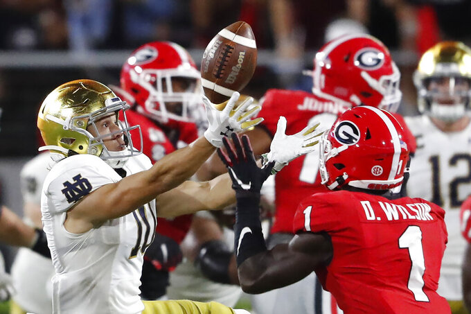 Notre Dame wide receiver Chris Finke (10) bobbles the ball as Georgia defensive back Divaad Wilson (1) makes an interception during the second half of an NCAA college football game, Saturday, Sept. 21, 2019, in Athens, Ga. Georgia won 23-17. (AP Photo/John Bazemore)