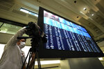 A TV crew films an electronic stock board showing reopened Japan's Nikkei 225 index at Tokyo Stock Exchange in Tokyo Friday, Oct. 2, 2020. Tokyo's market resumed trading Friday after a full-day outage due to a malfunction in its computer systems. (AP Photo/Eugene Hoshiko)