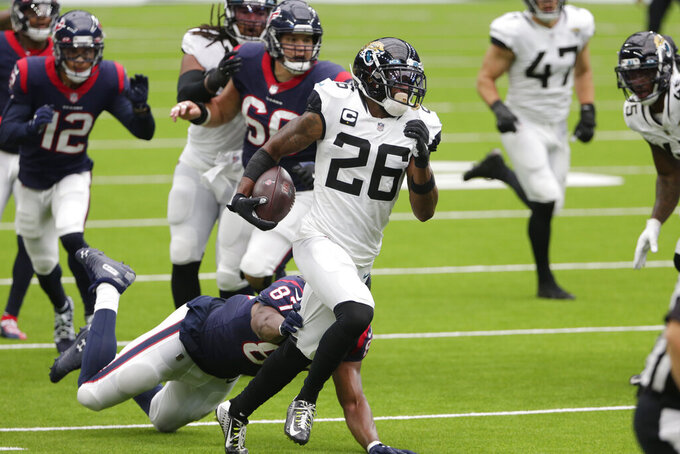 Jacksonville Jaguars free safety Jarrod Wilson (26) runs past Houston Texans tight end Darren Fells (87) after making an d interception during the second half of an NFL football game Sunday, Oct. 11, 2020, in Houston. (AP Photo/Michael Wyke)