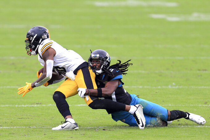 Pittsburgh Steelers wide receiver Diontae Johnson, left, is tackled by Jacksonville Jaguars cornerback Tre Herndon during the first half of an NFL football game, Sunday, Nov. 22, 2020, in Jacksonville, Fla. (AP Photo/Matt Stamey)