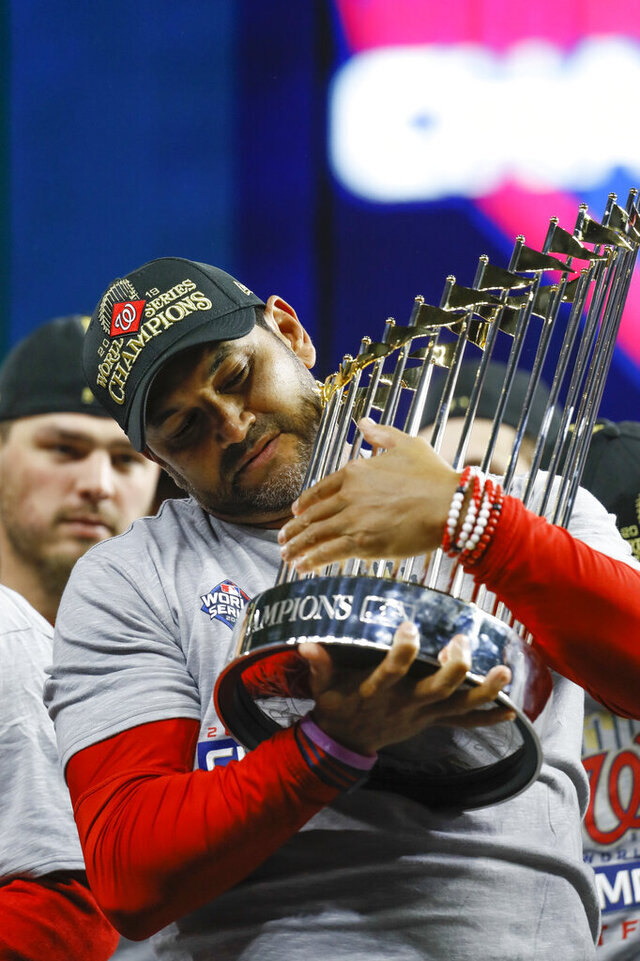 FILE - In this Oct. 30, 2019, file photo, Washington Nationals manager Dave Martinez celebrates after Game 7 of the baseball World Series against the Houston Astros in Houston. Martinez says the World Series champs will raise their banner and present their rings at their stadium with fans in attendance -- no matter how or when or if the 2020 season starts. Like his general manager, Mike Rizzo, Martinez is optimistic there will be a major league season this year and has been mapping out what a second spring training camp might look like. (AP Photo/Matt Slocum, File)