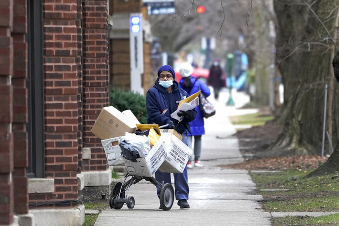 "FILE - A U.S. postal worker delivers packages, boxes and letters Tuesday, Dec. 22, 2020, along her route in the Hyde Park neighborhood of Chicago, just three days before Christmas.  Some Christmas gift-givers discovered their presents didn't arrive in time for the holiday despite ordering weeks ahead. The U.S. Postal Service says it faces ""unprecedented volume increases and limited employee availability due to the impacts of COVID-19.""  (AP Photo/Charles Rex Arbogast)"