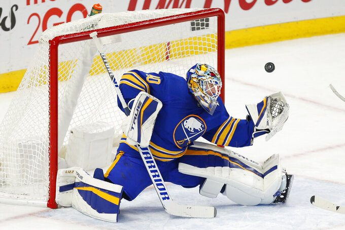 Buffalo Sabres goalie Carter Hutton (40) makes a save during the third period of an NHL hockey game against the New Jersey Devils, Sunday, Jan. 31, 2021, in Buffalo, N.Y. (AP Photo/Jeffrey T. Barnes)