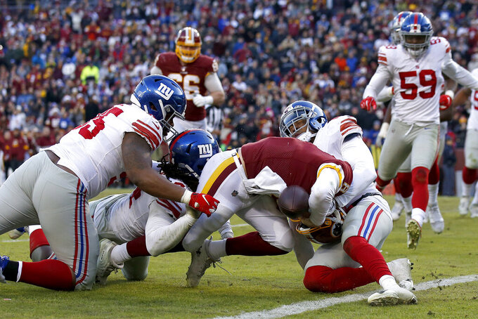 Washington Redskins quarterback Case Keenum (8) pushes his way to score on a keeper as New York Giants defenders, from left, B.J. Hill, Markus Golden and Deone Bucannon try to stop him during the second half of an NFL football game, Sunday, Dec. 22, 2019, in Landover, Md. (AP Photo/Alex Brandon)