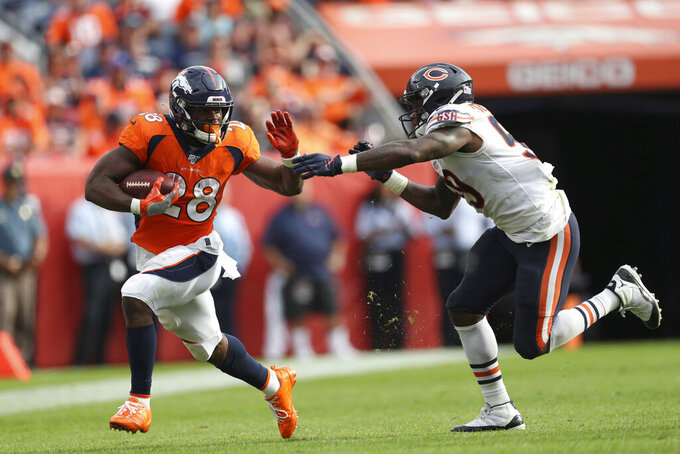 Denver Broncos running back Royce Freeman (28) tries to stiff-arm Chicago Bears inside linebacker Danny Trevathan (59) as Freeman carries the ball in an NFL game against the Chicago Bears, Sunday Sept. 15, 2019, in Denver. The Bears defeated the Broncos 16-14. (Margaret Bowles via AP)