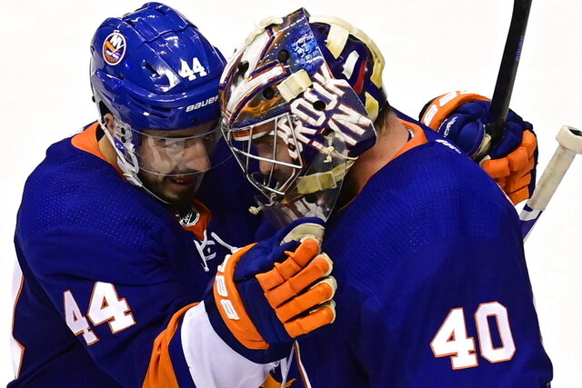 New York Islanders center Jean-Gabriel Pageau (44) celebrates with goaltender Semyon Varlamov (40) after defeating the Philadelphia Flyers in NHL Stanley Cup Eastern Conference playoff hockey game action in Toronto, Saturday, Aug. 29, 2020. (Frank Gunn/The Canadian Press via AP)