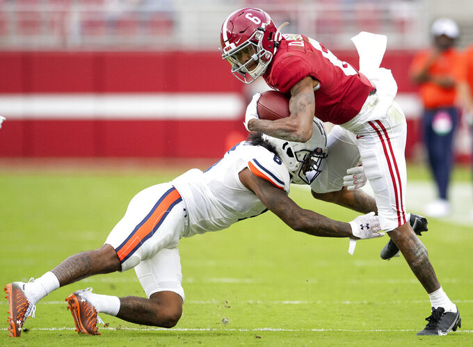 Auburn defensive back Christian Tutt, left, stops Alabama wide receiver DeVonta Smith during an NCAA college football game Saturday, Nov. 28, 2020, in Tuscaloosa, Ala. (Mickey Welsh/The Montgomery Advertiser via AP)