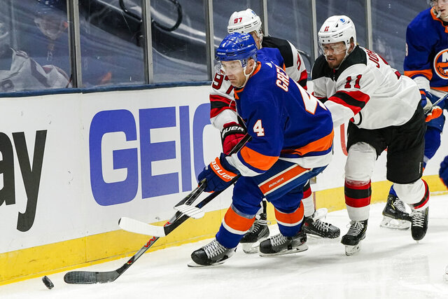 New York Islanders' Andy Greene (4) is defended by New Jersey Devils' Andreas Johnsson (11) and Nikita Gusev (97) during the third period of an NHL hockey game Thursday, Jan. 21, 2021, in Uniondale, N.Y. (AP Photo/Frank Franklin II)