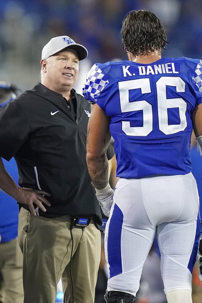 Kentucky head coach Mark Stoops speaks with Kentucky linebacker Kash Daniel (56) during the second half of an NCAA college football game between Kentucky and Eastern Michigan, Saturday, Sept. 7, 2019, in Lexington, Ky. (AP Photo/Bryan Woolston)