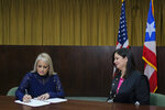 Justice Secretary Wanda Vazquez signs a document after she was sworn in as governor of Puerto Rico by Supreme Court Justice Maite Oronoz, right, in San Juan, Puerto Rico, Wednesday, Aug. 7, 2019 in San Juan Puerto Rico. Vazquez took the oath of office early Wednesday evening at the Puerto Rican Supreme Court, which earlier in the day ruled that Pedro Pierluisi's swearing in last week was unconstitutional. Vazquez was joined by her daughter Beatriz Diaz Vazquez and her husband Judge Jorge Diaz. (AP Photo/Dennis M. Rivera Pichardo)