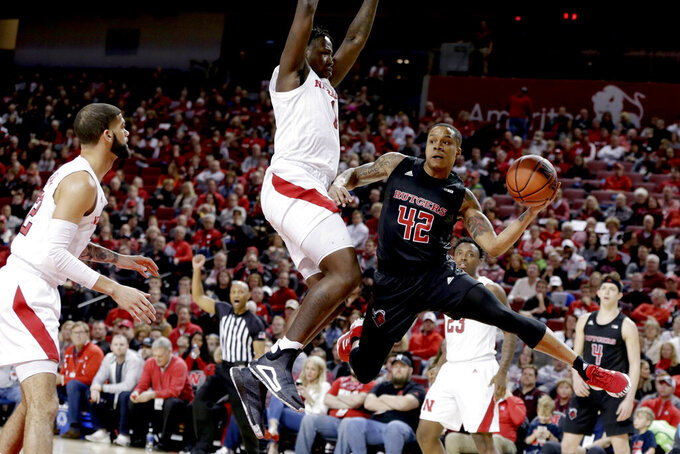 Rutgers' Jacob Young (42) passes the ball around Nebraska's Kevin Cross (1) during the first half of an NCAA college basketball game in Lincoln, Neb., Friday, Jan. 3, 2020. (AP Photo/Nati Harnik)