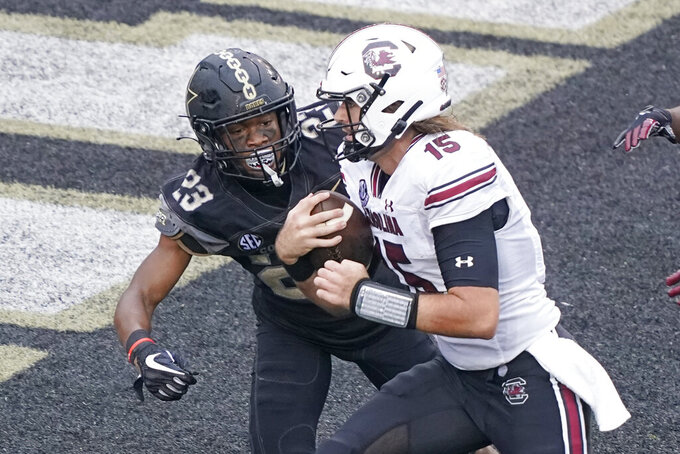 South Carolina quarterback Collin Hill (15) gets past Vanderbilt cornerback Jaylen Mahoney (23) as Hill runs 10 yards for a touchdown in the second half of an NCAA college football game Saturday, Oct. 10, 2020, in Nashville, Tenn. South Carolina won 41-7. (AP Photo/Mark Humphrey)