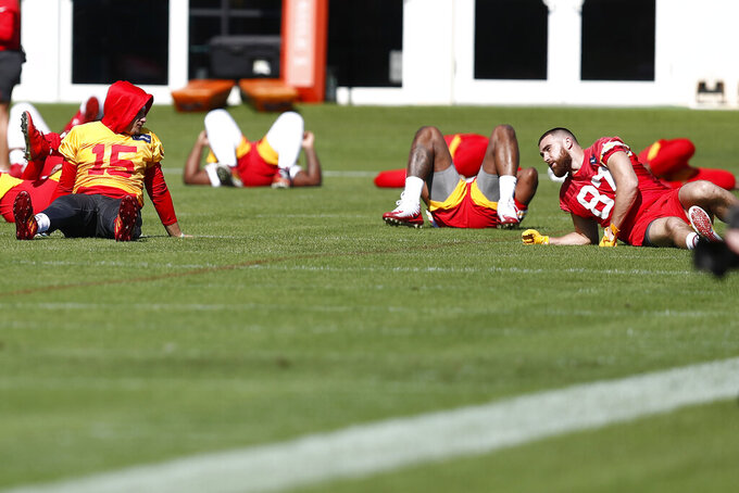 Kansas City Chiefs quarterback Patrick Mahomes (15) talks to tight end Travis Kelce (87) during practice on Wednesday, Jan. 29, 2020, in Davie, Fla., for the NFL Super Bowl 54 football game. (AP Photo/Brynn Anderson)