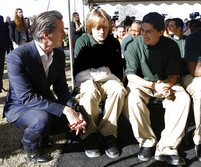 FILE - In this Jan. 22, 2019, file photo, Gov. Gavin Newsom talks with Juan Cruz Lopez Jr., far right, a youthful offender at the O.H. Close Youth Correctional Facility, in Stockton, Calif. Newsom signed a bill Wednesday, Sept. 30, 2020, that will phase out the state's remaining juvenile prisons, which currently hold about 750 youths, a move that Sen. Nancy Skinner called