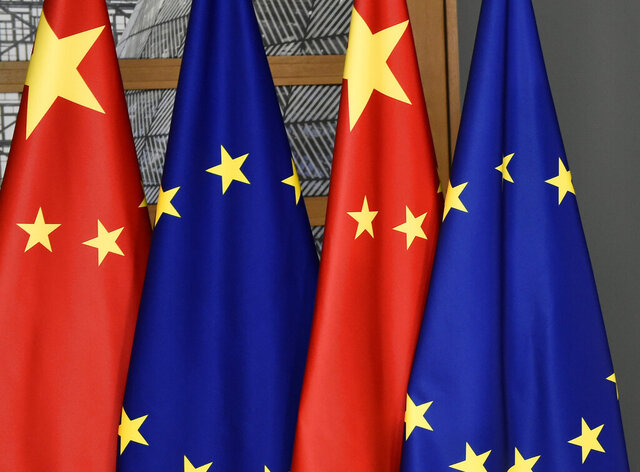 "FILE - In this file photo dated Tuesday, Dec. 17, 2019,  EU and Chinese flags at the Europa building in Brussels. China's European Union envoy on Wednesday Jan. 27, 2021, is urging the 27-nation European bloc to deepen its ties with his country even further and says he hopes the EU's desire for ""strategic autonomy"" will guide its foreign policy in the future .(John Thys/FILE via AP)"