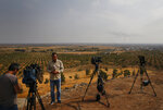 TV journalists work on a hilltop in Ceylanpinar, Sanliurfa province, southeastern Turkey, as in the background smoke billows from a fire in Ras al-Ayn, Syria, Sunday, Oct. 20, 2019. Turkey's defense ministry says one soldier has been killed amid sporadic clashes with Kurdish fighters in northern Syria, despite a U.S.-brokered cease-fire. The ministry also said it allowed a 39-vehicle humanitarian convoy to enter Ras al-Ayn, a key border town that's seen some of the heaviest fighting. (AP Photo/Lefteris Pitarakis)