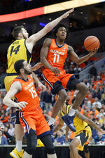 Illinois' Ayo Dosunmu (11) heads to the basket past teammate Giorgi Bezhanishvili (15) and Missouri's Reed Nikko (14) during the first half of an NCAA college basketball game Saturday, Dec. 21, 2019, in St. Louis. (AP Photo/Jeff Roberson)