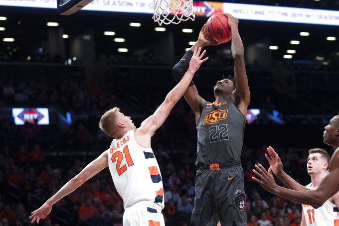 Oklahoma State forward Kalib Boone (22) goes to the basket against Syracuse forward Marek Dolezaj (21) during the first half of an NCAA college semi final basketball game in the NIT Season Tip-Off tournament, Wednesday, Nov. 27, 2019, in New York. (AP Photo/Mary Altaffer)