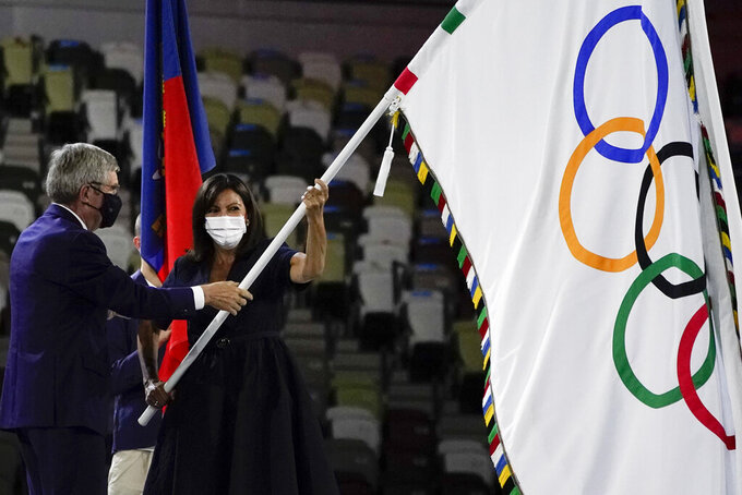 International Olympic Committee's President Thomas Bach gives the Olympic flag to Paris mayor Anne Hidalgo during the closing ceremony in the Olympic Stadium at the 2020 Summer Olympics, Sunday, Aug. 8, 2021, in Tokyo, Japan. (AP Photo/Jae C. Hong)