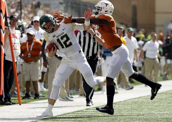 Baylor quarterback Charlie Brewer (12) is hit by Texas defensive back Kris Boyd (2) as he runs during the first half of an NCAA college football game, Saturday, Oct. 13, 2018, in Austin, Texas. (AP Photo/Eric Gay)