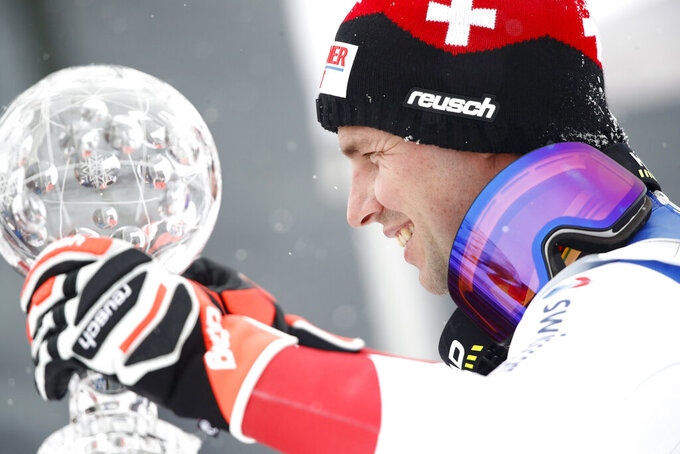 Switzerland's Beat Feuz holds the trophy of the alpine ski, men's World Cup downhill, in Lenzerheide, Switzerland, Wednesday, March 17, 2021. (AP Photo/Gabriele Facciotti)