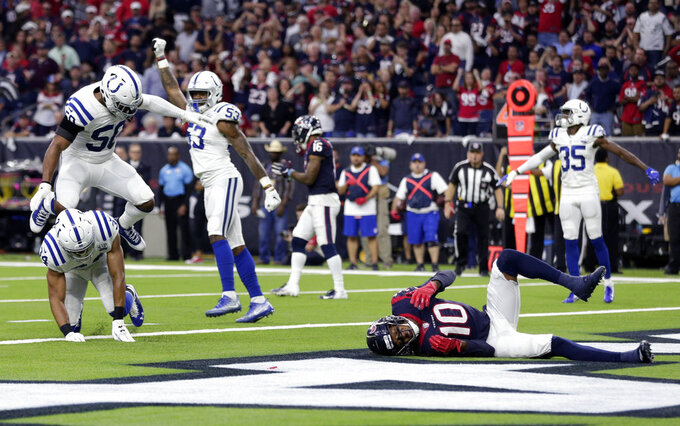 Indianapolis Colts defenders Mike Mitchell (34), Anthony Walker (50) and Darius Leonard (53) celebrate after breaking up a pass intended for Houston Texans wide receiver DeAndre Hopkins (10) on a fourth down during the first half of an NFL wild card playoff football game, Saturday, Jan. 5, 2019, in Houston. (AP Photo/Michael Wyke)