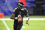 Baltimore Ravens quarterback Lamar Jackson rolls out against the Dallas Cowboys during the first half of an NFL football game, Tuesday, Dec. 8, 2020, in Baltimore. (AP Photo/Nick Wass)