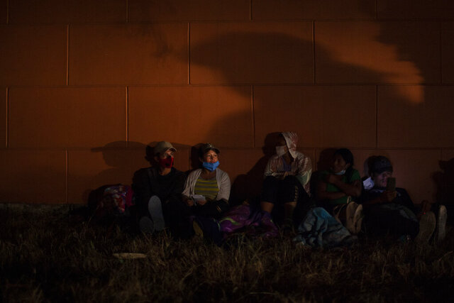 Honduran migrants hoping to reach the U.S. border rest on the side of a highway, as soldiers patrol the road in Vado Hondo, Guatemala, Saturday, Jan. 16, 2021. Guatemalan authorities estimated that as many as 9,000 Honduran migrants crossed into Guatemala as part of an effort to form a new caravan to reach the U.S. border. (AP Photo/Sandra Sebastian)