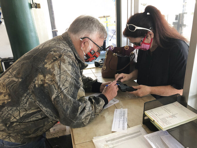 "In this April 9, 2021, photo, Terry Stephens, left, a sales worker at Ritchies Pawn Central, a store that was mentioned in J.D. Vance's book ""Hillbilly Elegy"", talks with Laura Stephens. Laura, who is no relation to Terry, was asking about a 9mm Taurus handgun she bought. She says her home has been broken into 4 times. Vance, whose book helped explain to the nation Donald Trump's popularity among the Appalachian working class, is ""thinking seriously"" about running for the U.S. Senate seat Republican two-term incumbent Rob Portman decided against seeking again in 2022. (AP Photo/Dan Sewell)"