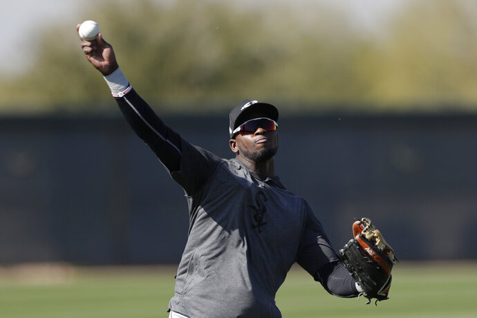 FILE - In this Monday, Feb. 17, 2020, file photo, Chicago White Sox center fielder Luis Robert throws the ball during spring training baseball in Phoenix. The 22-year-old Robert joins a formidable White Sox lineup after agreeing to a $50 million, six-year contract in January. (AP Photo/Gregory Bull, File)