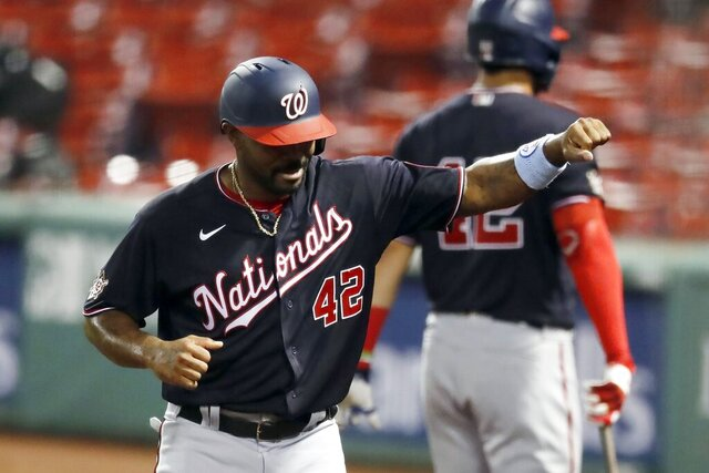 Washington Nationals' Howie Kendrick celebrates after scoring on a single by Adam Eaton during the third inning of a baseball game against the Boston Red Sox, Saturday, Aug. 29, 2020, in Boston. (AP Photo/Michael Dwyer)