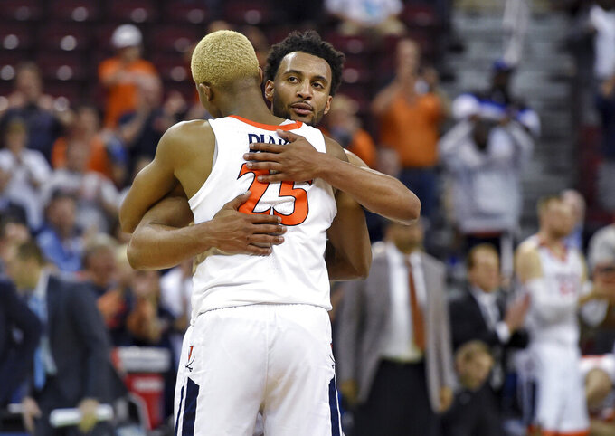 Virginia's Mamadi Diakite (25) hugs Braxton Key after Virginia defeated Oklahoma 63-51 in a second-round men's college basketball game in the NCAA Tournament in Columbia, S.C., Sunday, March 24, 2019. (AP Photo/Richard Shiro)