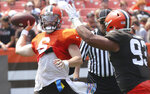Cleveland Browns quarterback Baker Mayfield, left, throws a pass away under pressure from defensive tackle Tommy Togiai during an Orange and Brown NFL football practice in Cleveland, Sunday, Aug. 8, 2021. (John Kuntz/The Plain Dealer via AP)