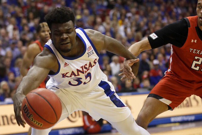 Kansas center Udoka Azubuike (35) reaches for the ball while covered by Texas Tech forward TJ Holyfield (22) during the first half of an NCAA college basketball game in Lawrence, Kan., Saturday, Feb. 1, 2020. (AP Photo/Orlin Wagner)