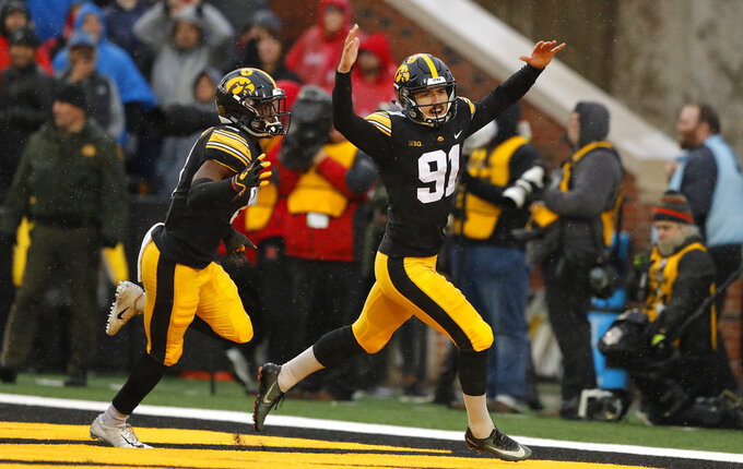 Iowa place kicker Miguel Recinos (91) celebrates with teammate Matt Hankins, left, after kicking a 41-yard field goal on the final play of an NCAA college football game against Nebraska, Friday, Nov. 23, 2018, in Iowa City, Iowa. Iowa won 31-28. (AP Photo/Charlie Neibergall)