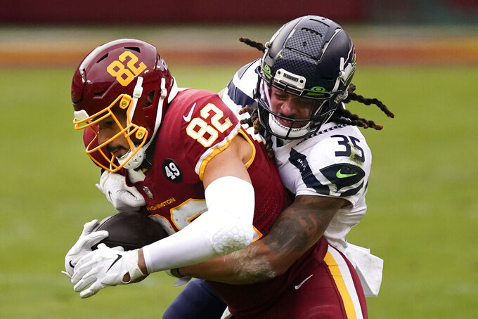 Washington Football Team tight end Logan Thomas (82) is stopped by Seattle Seahawks strong safety Ryan Neal (35) during the first half of an NFL football game between the Seattle Seahawks and Washington Football Team, Sunday, Dec. 20, 2020, in Landover, Md. (AP Photo/Andrew Harnik)