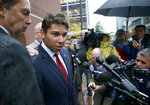 FILE — In this Thursday, Oct. 11, 2018 file photo, Fall River Mayor Jasiel Correia speaks to the media after leaving federal court in Boston. Correia heads to trial in federal court in April 2021 on charges that he stole more than $230,000 from investors in a smartphone app he created to pay for things like a Mercedes, casino trips and adult entertainment. As mayor, he's accused of convincing his chief of staff to give him half of her salary in order to keep her city job and extorting hundreds of thousands of dollars from marijuana businesses seeking to operate there. (Jonathan Wiggs/The Boston Globe via AP)
