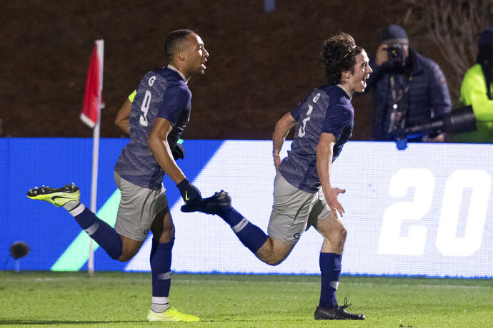 Georgetown's Paul Rothrock (3) celebrates with Derek Dodson (9) after scoring a goal during the first half of the NCAA college soccer championship against Virginia in Cary, N.C., Sunday, Dec. 15, 2019. (AP Photo/Ben McKeown)