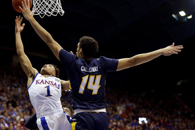 Kansas' Devon Dotson (1) shoots under pressure from UNC Greensboro's Kyrin Galloway (14) during the first half of an NCAA college basketball game Friday, Nov. 8, 2019, in Lawrence, Kan. (AP Photo/Charlie Riedel)