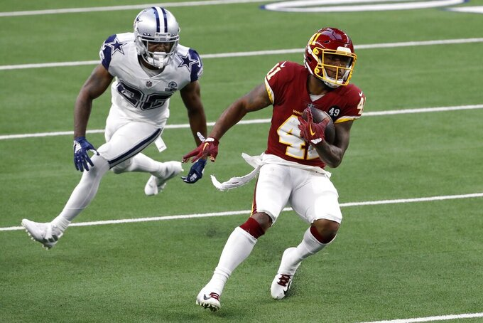 Dallas Cowboys cornerback Jourdan Lewis (26) is unable to stop Washington Football Team running back J.D. McKissic (41) from reaching the end zone for a touchdown in the first half of an NFL football game in Arlington, Texas, Thursday, Nov. 26, 2020. (AP Photo/Roger Steinman)