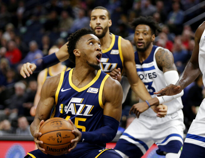 Utah Jazz guard Donovan Mitchell (45) drives on the Minnesota Timberwolves with Utah Jazz center Rudy Gobert and Minnesota Timberwolves forward Robert Covington behind the play during the first quarter of an NBA basketball game Wednesday, Nov. 20, 2019 in Minneapolis. (AP Photo/Andy Clayton-King)